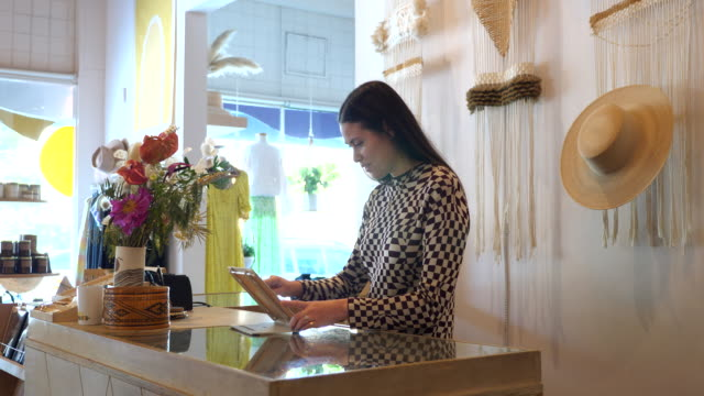 ms shop owner working on digital tablet behind counter in clothing boutique - working stock videos & royalty-free footage