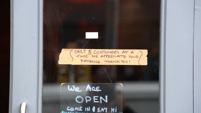 shop sign encouraging 'social distancing' as the uk government announces all cafes pubs and restaurants must close from this evening in a bid to stop... - merchandise stock videos & royalty-free footage