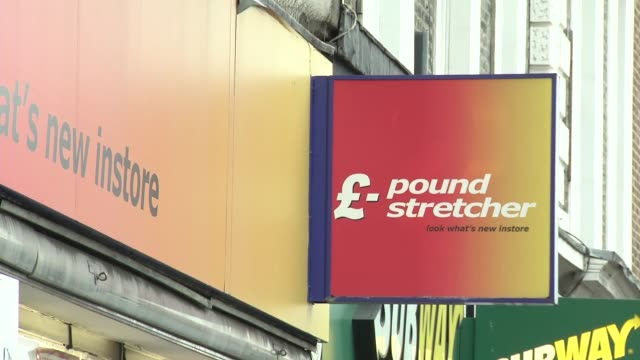 Shop sign for 'Pound Stretcher' store PULL OUT to high street people walking past / Shop sign / Ripped shop sign / Children's toys in shop window /...