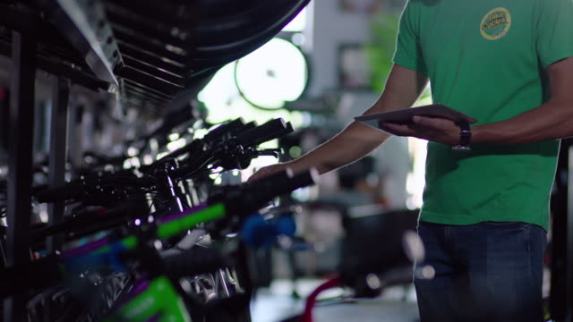 shop worker enters data on tablet computer and hangs price tags on new bikes - net sports equipment stock videos and b-roll footage
