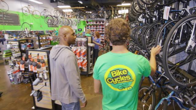 shop worker walks customer through store and shows off different bike models - verkäufer stock-videos und b-roll-filmmaterial