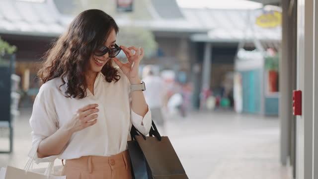 vidéos et rushes de femme shopaholic regardant dans le magasin dans le centre commercial - shopaholic