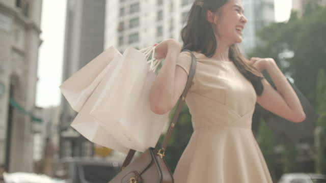 shopaholic woman turnaround with her shopping bags - shopaholic stock videos & royalty-free footage