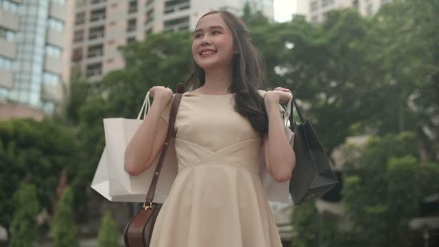 vidéos et rushes de retournement de femme shopaholic avec ses sacs à provisions - shopaholic