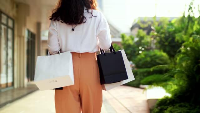 vidéos et rushes de femme shopaholic marchant à outlet - shopaholic
