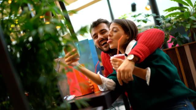 vidéos et rushes de shopaholics dans un centre commercial de prendre des selfies. - bouche humaine