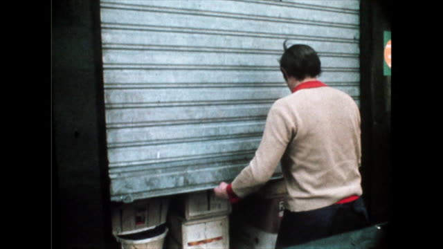 shopkeeper closes shop and market stalls are closed; 1969 - persiana caratteristica architettonica video stock e b–roll