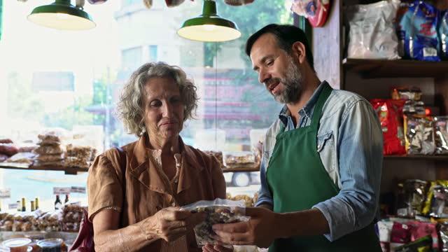 shopkeeper explaining product to senior female customer - customer focused stock videos & royalty-free footage
