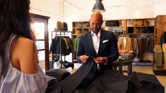vídeos de stock e filmes b-roll de ms shopkeeper helping customer choose from a selection of denim in mens clothing boutique - duas pessoas