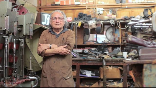 stockvideo's en b-roll-footage met ms shopkeeper posing in his shoe repair shop / santa monica, california, united states - breedbeeldformaat
