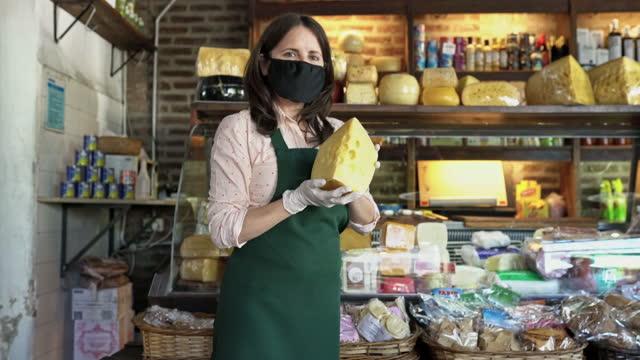 stockvideo's en b-roll-footage met winkelier presenteren stuk kaas in de tijd van covid-19 - dairy product
