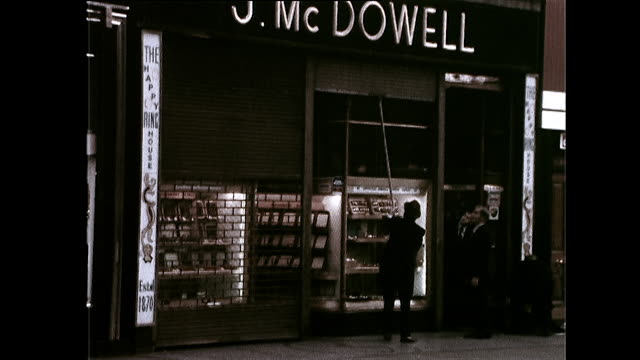 shopkeeper pulls down the shutter on shop front; dublin, 1972 - shutter stock videos & royalty-free footage
