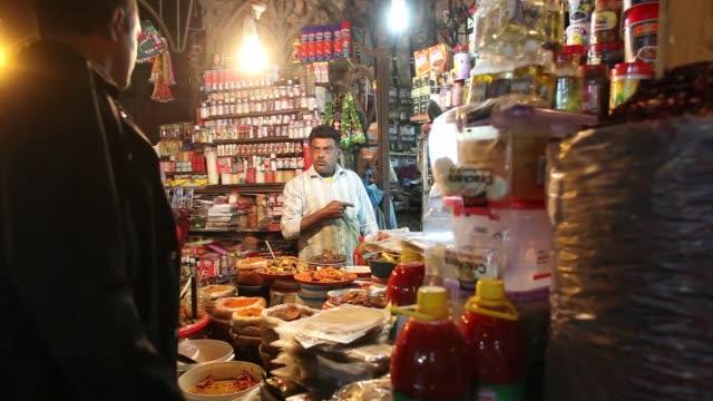 shopkeeper serves customers at a market stall at night in karachi, pakistan, on thursday, dec. 14 a shopkeeper works at a market stall at night, a... - ナイトイン点の映像素材/bロール