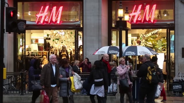 A shopper carries Topman shopping bags on Oxford Street in London UK on Tuesday Nov 17 Shoppers cross Oxford Street beneath suspended Christmas...