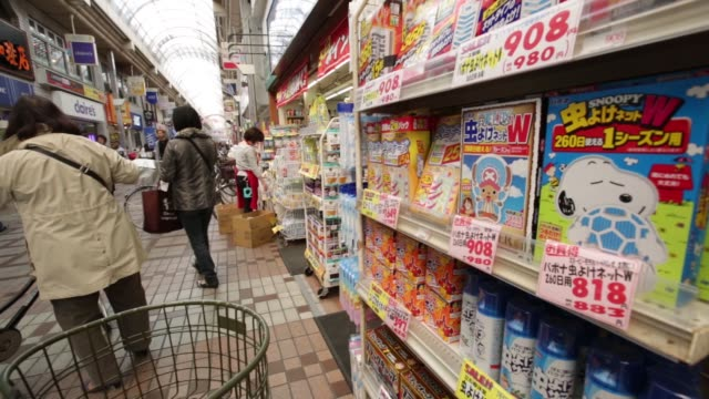 A shopper collects a basket in a shopping arcade in Tokyo Japan on Monday March 23 Pedestrians walk past a store in a shopping arcade A woman browses...