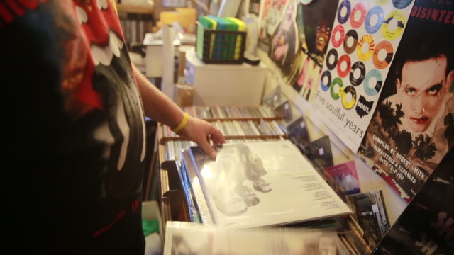 a shopper goes through his stack of records he found at landlocked records during record store day april 16 2016 in bloomington indiana record store... - ミュージックショップ点の映像素材/bロール