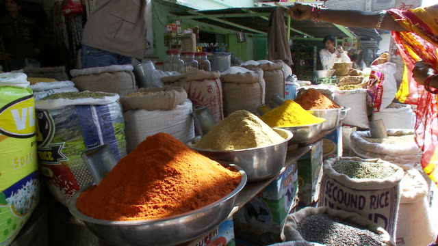 A shopper in a sari purchases spices from a vendor at a market.