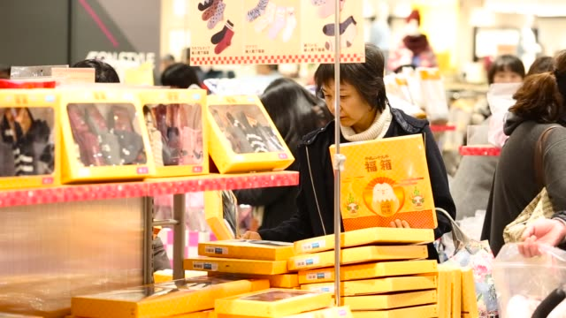 shopper looks at fukubukuro lucky bags at the aeon lake town shopping mall, operated by aeon retail co, a unit of aeon co, on the first day of the... - 百貨店点の映像素材/bロール