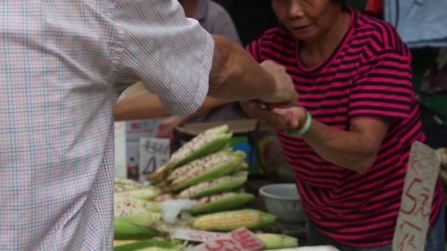 a shopper pays a vendor for purchased vegetables medium view of canteloupes at a fruit stall shoppers buy grapes at a fruit stall in mong kok... - mong kok stock videos and b-roll footage