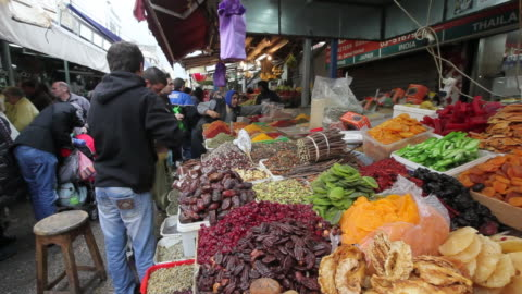a shopper selects products from a stall in the carmel market in tel aviv, israel. - テルアビブ点の映像素材/bロール