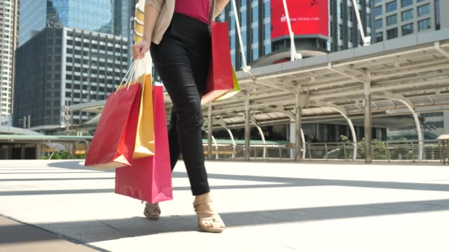 shopper walking with shopping bags in the city - shopping bag stock videos & royalty-free footage