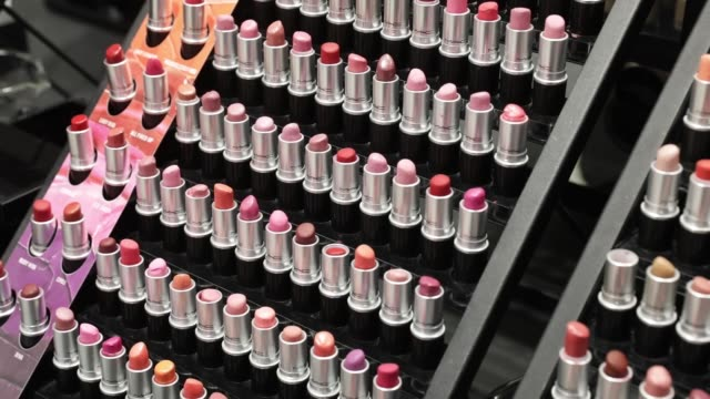 a shopper walks past a mac cosmetics inc store in the raffles city shopping mall in shanghai china on wednesday may 31 lipsticks sit on display at a... - cosmetics stock videos & royalty-free footage