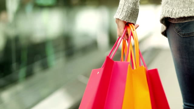 shopper with shopping bags on escalator - shopping mall stock videos & royalty-free footage