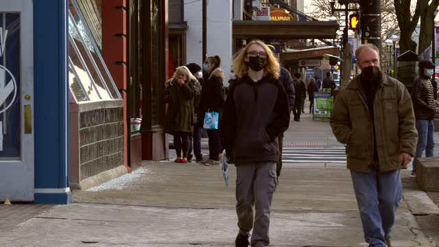 stockvideo's en b-roll-footage met shoppers and pedestrians alike wear face masks while outdoors during the holiday season in downtown ann arbor, michigan on december 23. while mask... - straatnaambord