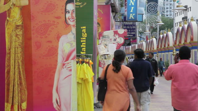 Shoppers and pedestrians pass brightly colored shop displays in Little India.