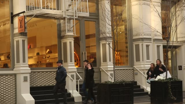 shoppers and pedestrians pass by louis vuitton in new york, new york, monday march 13, 2017. shots: wide shot of louis vuitton store with people... - louis vuitton designer label stock videos & royalty-free footage