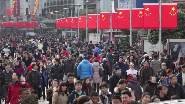 Shoppers and pedestrians walk through the East Nanjing Road shopping district of Shanghai Shopping district in Shanghai on February 02 2013 in...