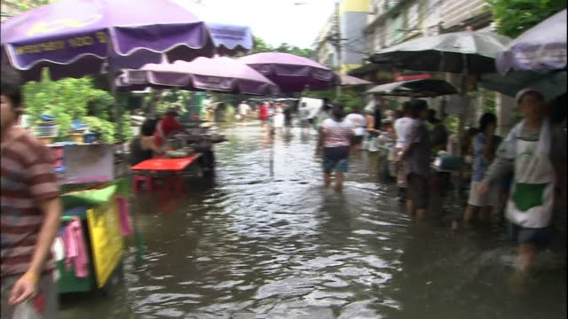 vídeos de stock e filmes b-roll de shoppers and vendors still attend a chinatown market in thailand despite kneehigh flooding - rio chao phraya