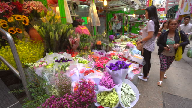Shoppers at a flower market stall, Hong Kong