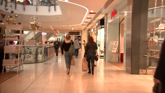 stockvideo's en b-roll-footage met shoppers at intu lakeside shopping centre at christmas; england: essex: thurrock: lakeside shopping centre: int people along carrying shopping bags /... - shopping centre