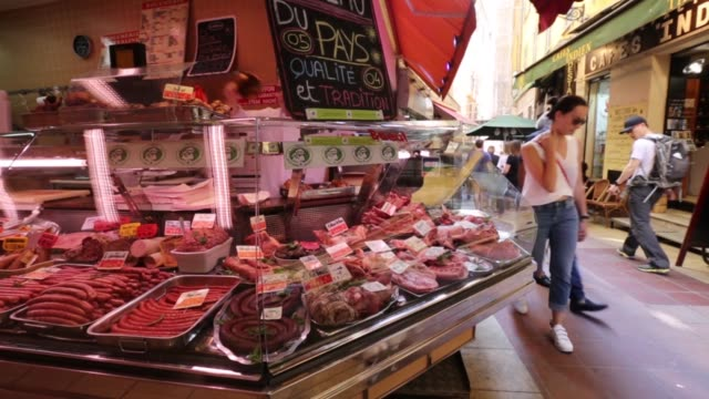 Shoppers browse meat for sale in a butcher's counter in an open air market in the old town in Nice France on Thursday May 14 2015