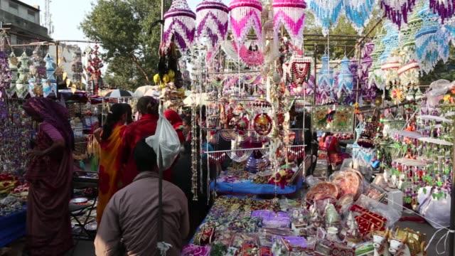 vídeos y material grabado en eventos de stock de shoppers browse necklaces at a market stall in ahmedabad, gujarat, india, on wednesday, jan. 11 decorations hang on display at a market stall,... - iva