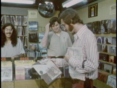 vídeos de stock e filmes b-roll de shoppers browse records at a sam goody music store in 1970. - 1970