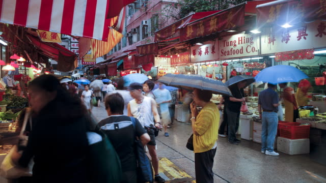 shoppers browse the traditional chinese stalls in wanchai market, hong kong island, hong kong, china, time-lapse - wanchai stock videos and b-roll footage
