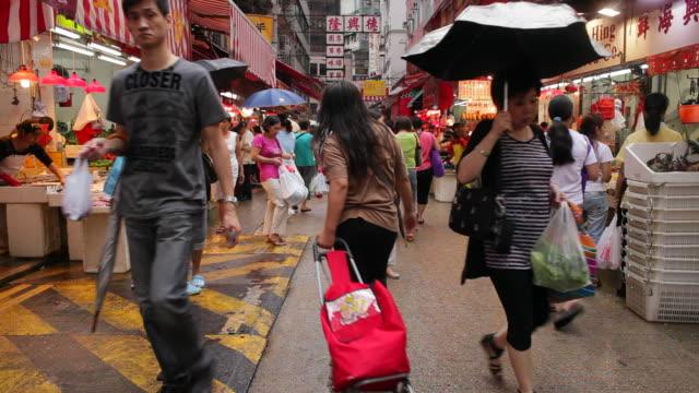 vídeos de stock, filmes e b-roll de shoppers browse through a market in wan chai. - wan chai
