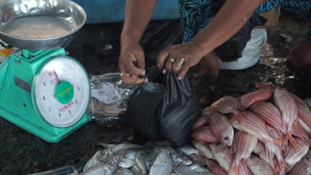 Shoppers buy fish in the fish market area of the Central Market in Kota Kinabalu Sabah Malaysia on Sunday July 30 Close up a vendor weighs fish on a...