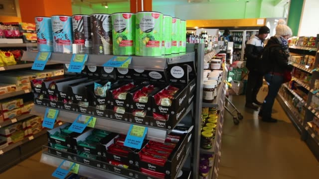 vídeos de stock, filmes e b-roll de shoppers choose products in the aisle of a veganz vegan grocery store as packages of vegan protein shake stand on a shelf on february 2 2018 in... - vegan