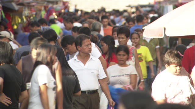 Shoppers crowd a busy market street in Manila.