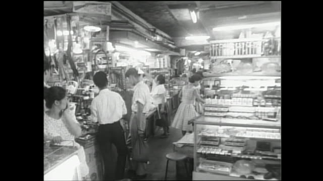shoppers drowse merchandise in an ameyoko shop in tokyo, japan. - showa period stock videos and b-roll footage