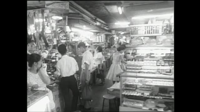stockvideo's en b-roll-footage met shoppers drowse merchandise in an ameyoko shop in tokyo, japan. - showaperiode