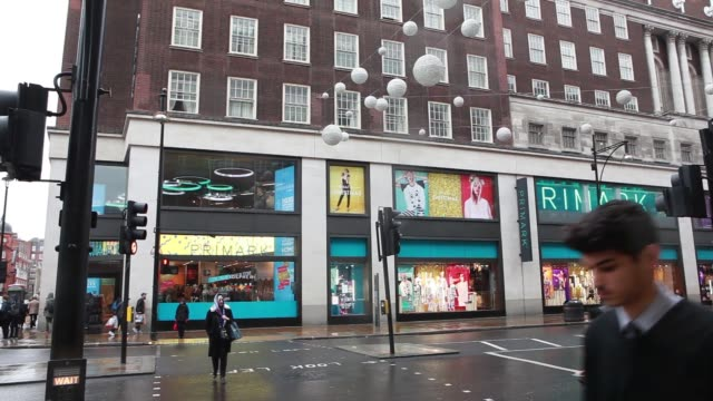 shoppers enter and exit at the entrance to a primark store traffic passes a bus stop outside a primark store pan r l of the exterior a primark... - window display stock videos and b-roll footage