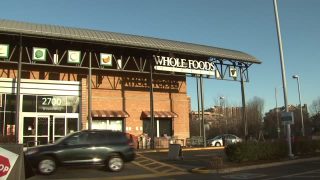 shoppers enter and exit whole foods market on a sunny winter day - whole foods market stock videos and b-roll footage