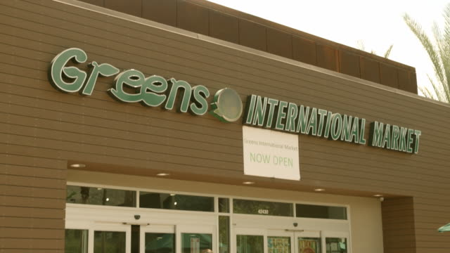 TD shoppers entering Greens International Market building as sliding doors open