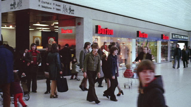 1973 montage shoppers exploring a new shopping concourse near liverpool / england, united kingdom - teenager alter stock-videos und b-roll-filmmaterial
