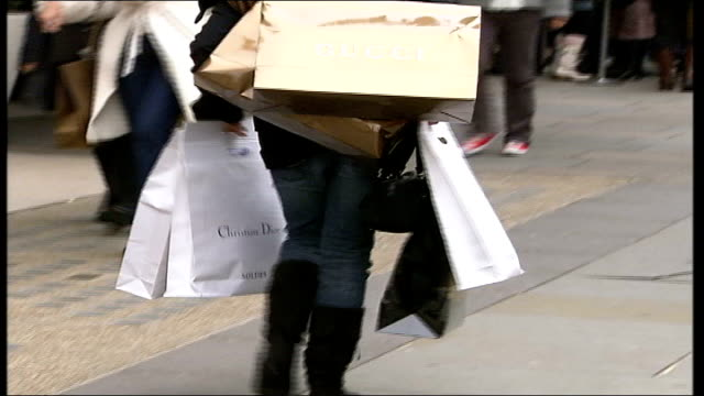 shoppers hit the high streets for christmas sales; england: london: ext shoppers waiting outside fendi store as woman exits carrying lots of shopping... - carrying stock videos & royalty-free footage