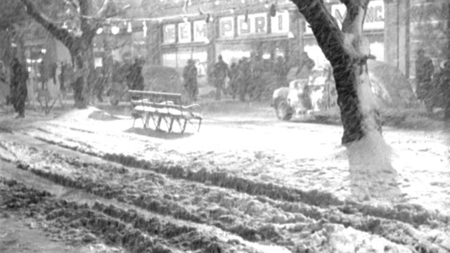 shoppers hurry as winds blow heavy snow and christmas decorations on a main street. - 1946 stock videos & royalty-free footage